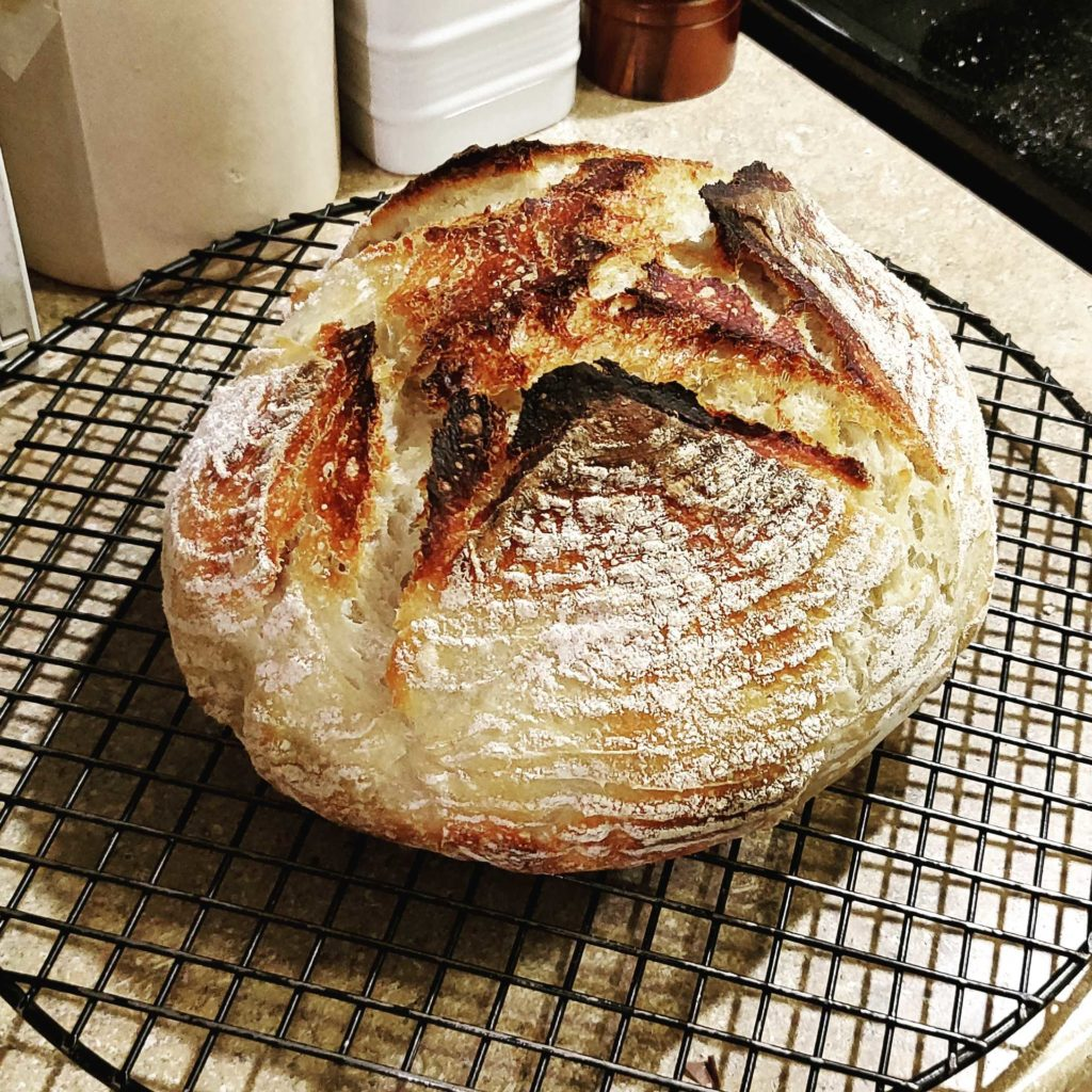 A sourdough boule, with basket-marks and flour on it, and slashed in a cross on top.
